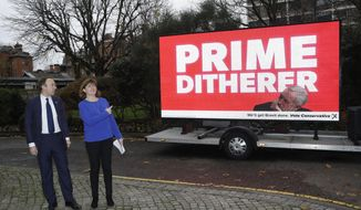 In this Monday, Nov. 25, 2019, file photo, British Conservative party Health Secretary Matt Hancock and his party colleague the Secretary of State for Digital, Culture, Media & Sport Nicky Morgan, in London as they launch their party's digital election campaign poster highlighting what they see as the opposition Labour Party leader Jeremy Corbyn's indecision. Lawmakers have called for sweeping reforms to protect democracy in the digital age, but the government failed to act in time for the upcoming Dec. 12 General Election, as political parties are mining social media cyberspace for votes. (AP Photo/Matt Dunham, File)