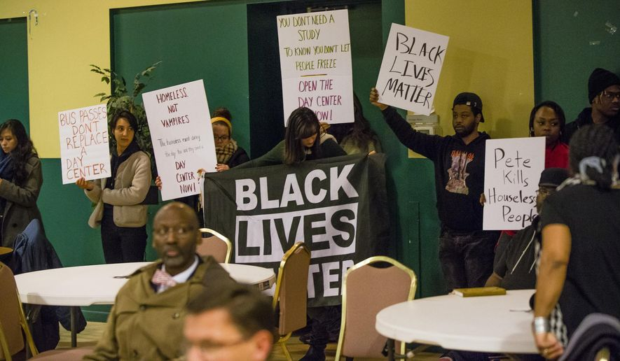Protesters hold signs during a gathering of community leaders to discuss Mayor Pete Buttigieg's work Wednesday, Dec. 4, 2019 at the Charles Martin Center in South Bend, Indiana.  (Michael Caterina/South Bend Tribune via AP)