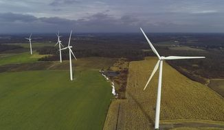 In this Nov. 25, 2019 photo, wind turbines slowly rotate over corn fields in Warsaw, N.Y. Renewable energy groups are pushing New York to help meet its ambitious climate change goals by charging electric generators for the carbon pollution they create. Putting a price on carbon will help New York meets its aggressive goal of 70% of its electricity coming from wind, solar and other renewable sources by 2030, the Alliance for Clean Energy New York said in a report. (AP Photo/Julie Jacobson)