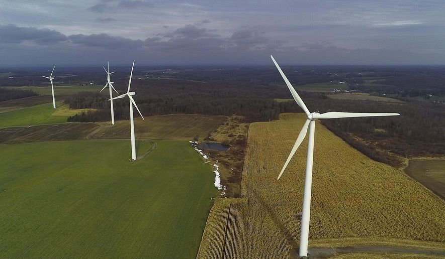 In this Nov. 25, 2019, photo, wind turbines slowly rotate over corn fields in Warsaw, N.Y. Renewable energy groups are pushing New York to help meet its ambitious climate change goals by charging electric generators for the carbon pollution they create. Putting a price on carbon will help New York meets its aggressive goal of 70% of its electricity coming from wind, solar and other renewable sources by 2030, the Alliance for Clean Energy New York said in a report. (AP Photo/Julie Jacobson) **FILE**