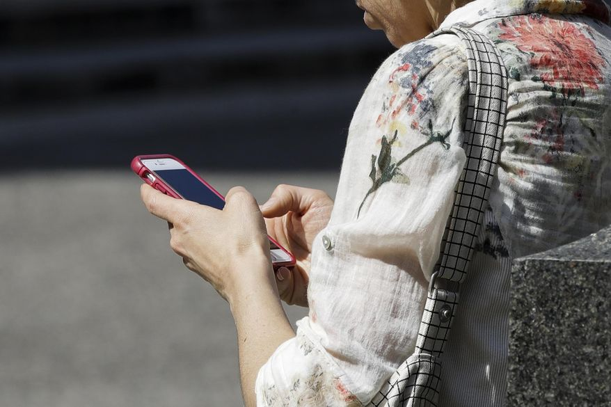 In this April 8, 2019, file photo, a woman browses her smartphone in Philadelphia. Accidental cuts and bruises to the face, head and neck from cellphones are sending increasing numbers of Americans to the emergency room, according to a study that estimates 76,000 cases over nine years. (AP Photo/Matt Rourke, File)