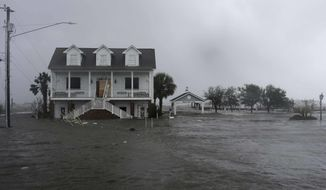 FILE - In this Sept. 14, 2018, file photo, high winds and water surround a house as Hurricane Florence hits Swansboro N.C. Historic coastal cities in the Southeast U.S. have survived disease outbreaks, wars and hurricanes over the past three centuries. Now they are trying to figure how to survive rising seas from climate change. (AP Photo/Tom Copeland, File)