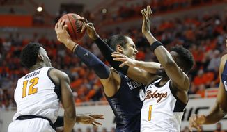 Georgetown's Omer Yurtseven (44) reaches for the ball between Oklahoma State's Cameron McGriff (12) and Jonathan Laurent (1) during an NCAA college basketball game in Stillwater, Okla., Wednesday, Dec. 4, 2019. (Bryan Terry/The Oklahoman via AP) **FILE**