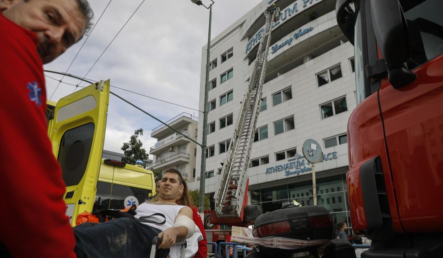 Paramedics carry a man to an ambulance as firefighters are seen on a ladder, some minutes after a fire broke up in the Athenaeum Palace hotel in Athens on Thursday, Dec. 5, 2019. A fire has broken out at a luxury hotel in the Greek capital, with fire crews evacuating the building and using ladders to rescue several people.(AP Photo/Petros Giannakouris)