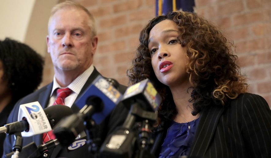 In this Dec. 3, 2019, photo. Maryland corrections secretary Robert Green, left, listens as Maryland State Attorney Marilyn Mosby, right, speaks during a news conference announcing the indictment of correctional officers, in Baltimore. (AP Photo/Julio Cortez) **FILE**
