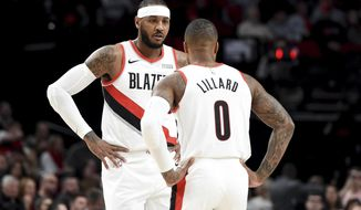 Portland Trail Blazers forward Carmelo Anthony, left, speaks with guard Damian Lillard, right, during a time out in the first half of an NBA basketball game against the Sacramento Kings in Portland, Ore., Wednesday, Dec. 4, 2019. (AP Photo/Steve Dykes)