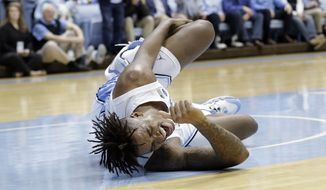 North Carolina forward Armando Bacot (5) grimaces in pain following an injury during the first half of an NCAA college basketball game against Ohio State in Chapel Hill, N.C., Wednesday, Dec. 4, 2019. (AP Photo/Gerry Broome)