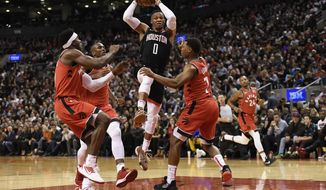 Houston Rockets guard Russell Westbrook (0) controls the ball between Toronto Raptors' defenders, left to right, Terence Davis, Serge Ibaka and Kyle Lowry during second half NBA action in Toronto on Thursday, Dec. 5, 2019. (Nathan Denette/The Canadian Press via AP)