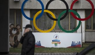 Olympic Rings and a model of Misha the Bear Cub, the mascot of the Moscow 1980 Olympic Games, left, are seen in the yard of Russian Olympic Committee building in Moscow, Russia, Thursday, Nov. 28, 2019. The WADA committee has proposed a package of sanctions including a four-year ban on hosting major events in Russia and a similar four-year sanction on Russians competing in top events like the Olympics, though they could enter as neutrals. (AP Photo/Pavel Golovkin)