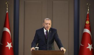 Turkey's President Recep Tayyip Erdogan speaks before departing to attend a NATO leader's summit in London, in Ankara, Turkey, Tuesday, Dec. 3, 2019. Erdogan says there is no change in Turkey's position that is holding up a NATO defense proposal for Poland and Baltic nations until the alliance supports Ankara's concerns related to Syrian Kurdish fighters. (Presidential Press Service via AP, Pool)