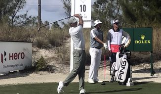 Tiger Woods tees off at the 10th hole of Albany Golf Club as Bubba Watson and his caddie look during the second round of the Hero World Challenge in Nassau, Bahamas, Thursday Dec. 5 2019.  (AP Photo/Doug Ferguson)