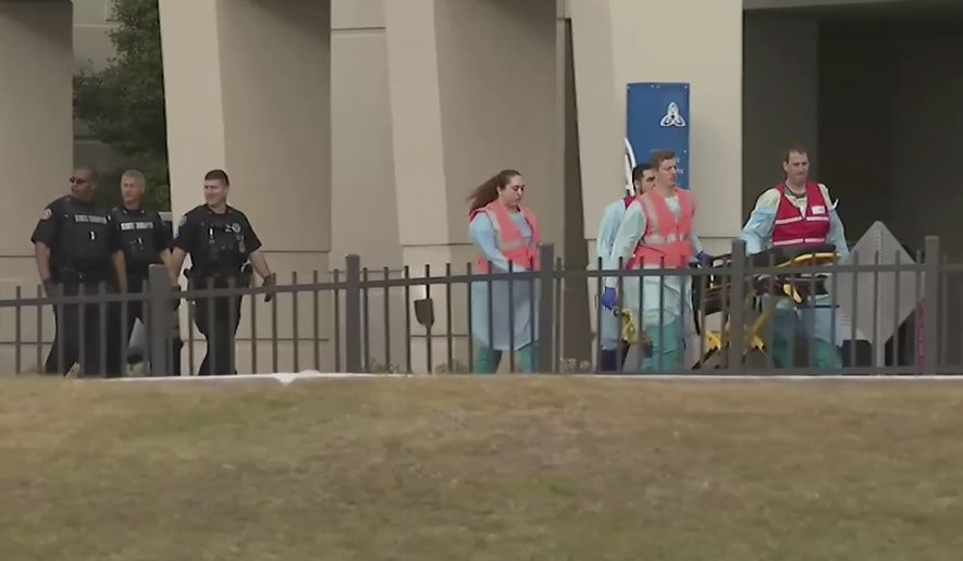 This photo taken from video provided by WEAR-TV shows emergency responders near the Naval Air Base Station in Pensacola, Fla., Friday, Dec. 6, 2019.  The US Navy is confirming that an active shooter and one other person are dead after gunfire at the Naval Air Station in Pensacola. Area hospital representatives tell The Associated Press that at least 11 people were hospitalized. The base remains locked down amid a huge law enforcement response.  (WEAR-TV via AP)