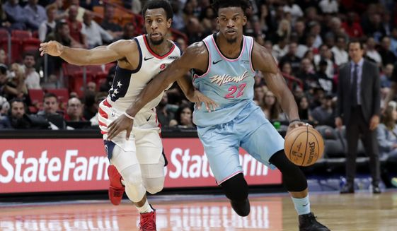 Miami Heat forward Jimmy Butler (22) drives past Washington Wizards center Thomas Bryant during the second half of an NBA basketball game, Friday, Dec. 6, 2019, in Miami. The Heat won 112-103. (AP Photo/Lynne Sladky) ** FILE **