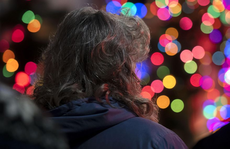 In this Thursday, Dec. 5, 2019, photo a woman watches as a brightly lit float passes by during the Christmas parade Thursday night in downtown Bristol, Va. (Andre Teague/Bristol Herald Courier via AP)