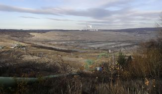 The Turow lignite coal mine near the town of Bogatynia, Poland, Tuesday, Nov. 19, 2019. The Turow lignite coal mine in Poland has an impact on the environment and communities near the border of three neighboring countries, the Czech Republic, Germany and Poland. Plans to further expand the huge open pit mine have caused alarm among residents who fear things might get even worse. (AP Photo/Petr David Josek)