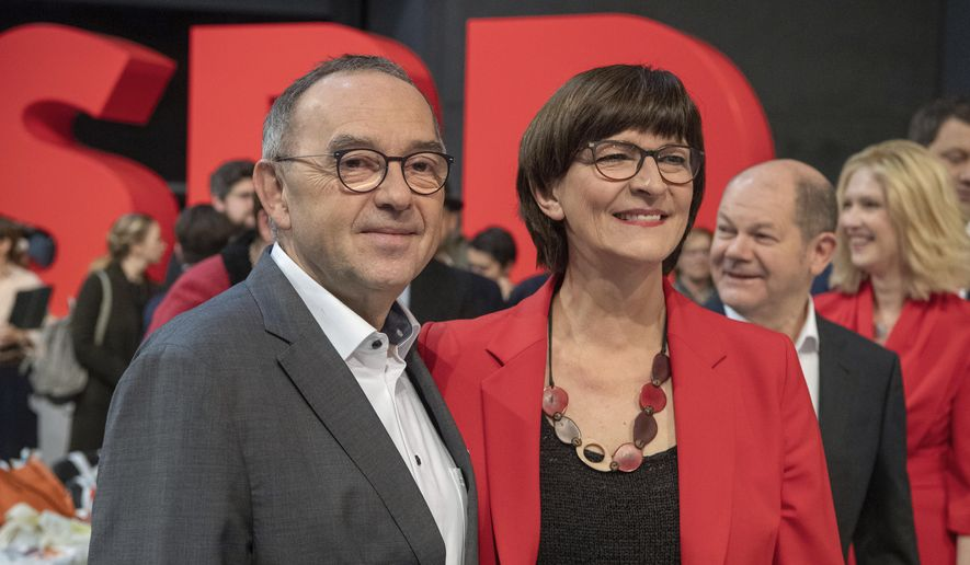 Norbert Walter-Borjans stands alongside Saskia Esken, and Finance Minister Olaf Scholz, from left, at the beginning of the German Social Democrats, SPD, federal party conference in Berlin, Germany, Friday, Dec. 6, 2019. Members of the center-left party have choosen the left-leaning duo Norbert Walter-Borjans and Saskia Esken as their new leaders. This has to be confirmed by the delegates at the party meeting. (Bernd von Jutrczenka/dpa via AP)