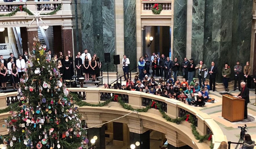 "Wisconsin Gov. Tony Evers prepares to light the Wisconsin Capitol tree that he calls a ""holiday tree"" Friday, Dec. 6, 2019 in Madison, Wis. A choir sings songs including ""O Christmas Tree"" and ""O Come All Ye Faithful"" during the event. (AP Photo/Scott Bauer)"