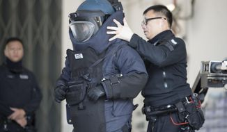 A police officer from the bomb disposal squad putting on protective gear during a demonstration for media in Hong Kong, Friday, Dec. 6, 2019. Hong Kong's much-maligned police force provided a rare behind-the-scenes look Friday at its bomb disposal squad to show the potentially deadly destructive force of homemade explosives seized during months of protests that have shaken the Chinese territory. (AP Photo/Vincent Thian)