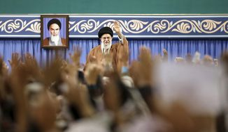 """FILE - In this Nov. 27, 2019, file photo released by the official website of the office of the Iranian supreme leader, Supreme Leader Ayatollah Ali Khamenei waves to members of the Revolutionary Guard's all-volunteer Basij force in a meeting in Tehran, Iran. Khamenei on Wednesday, Dec. 4, 2019, reportedly called on judicial officials to treat those detained in recent nationwide protests with """"Islamic mercy"""" after authorities acknowledged security forces shot and killed demonstrators nationwide. A portrait of the late revolutionary founder Ayatollah Khomeini hangs in background. (Office of the Iranian Supreme Leader via AP, File)"""