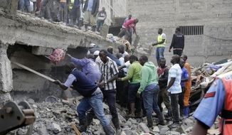 People at the scene of a collapsed building in in Tasia Embakasi, an east neighbourhood of Nairobi, Kenya on Friday Dec. 6, 2019.  A six-story building collapsed in Kenya's capital on Friday, officials said, with people feared to be trapped in the debris. Police say people have been rescued by residents using their bare hands.(AP Photo/Khalil Senosi)