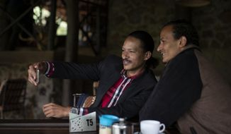 In this photo taken Wednesday, Oct. 30, 2019, Steven Lacchin, 39, left, takes a selfie with Gerald Erebon, 30, right, who DNA tests indicate is his half-brother, as they meet for the first time in Nairobi, Kenya. An Associated Press story on the front page of a newspaper in Nairobi brought together the two Kenyan men - one who knew that his father was an Italian missionary priest, and the other who wanted proof that he was the son of the same priest. (AP Photo/Ben Curtis)