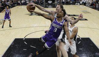 Sacramento Kings guard Yogi Ferrell (3) is blocked by San Antonio Spurs center Jakob Poeltl during the first half of an NBA basketball game in San Antonio, Friday, Dec. 6, 2019. (AP Photo/Eric Gay)