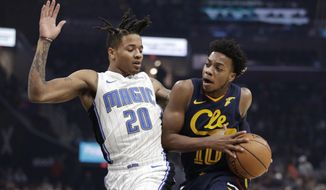 Cleveland Cavaliers' Darius Garland (10) drives past Orlando Magic's Markelle Fultz (20) in the first half of an NBA basketball game, Friday, Dec. 6, 2019, in Cleveland. (AP Photo/Tony Dejak)