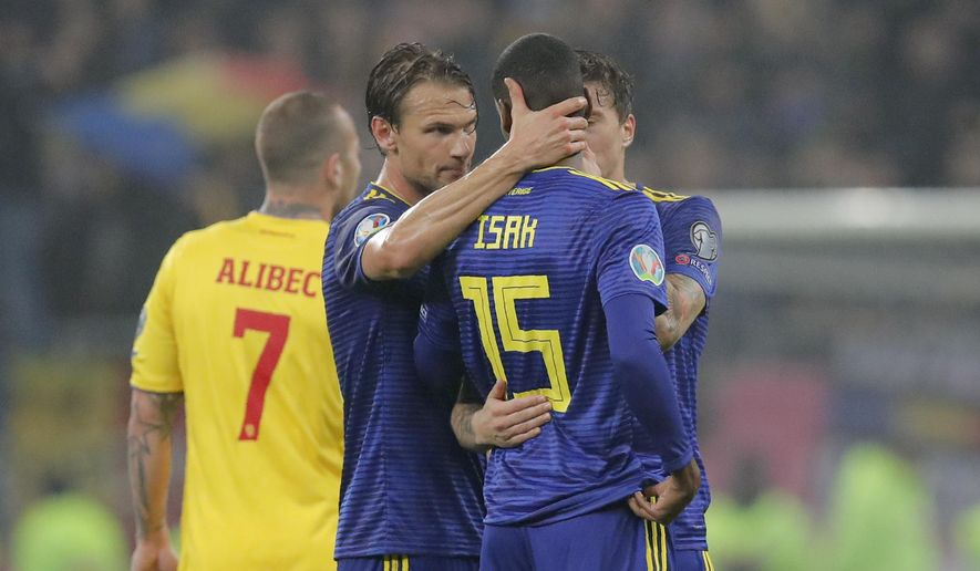Team mates hug Sweden's Alexander Isak after referee Daniele Orsato briefly stopped the game following alleged racist chants against the player during the Euro 2020 group F qualifying soccer match between Romania and Sweden on the National Arena stadium in Bucharest, Romania, Friday, Nov. 15, 2019. (AP Photo/Vadim Ghirda)