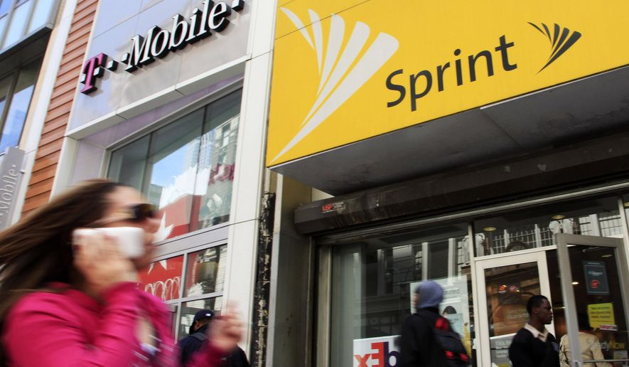 FILE - In this April 27, 2010 file photo, a woman using a cell phone walks past T-Mobile and Sprint stores in New York. T-Mobile, in its attempt to buy Sprint for $26.5 billion, shrinking the major wireless companies to three from four and creating another phone giant to rival AT&T and Verizon, has already notched approvals from federal national-security, telecommunications and antitrust regulators. Now it must convince a federal court judge in New York that the 14 state attorneys general suing to stop its deal are wrong. (AP Photo/Mark Lennihan, File)