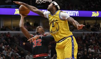 Chicago Bulls' Kris Dunn (32) goes up for a shot against Golden State Warriors' Willie Cauley-Stein (2) during the second half of an NBA basketball game Friday, Dec. 6, 2019, in Chicago. Golden State won 100-98. (AP Photo/Paul Beaty)