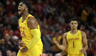 Maryland forward Donta Scott (24) reacts after scoring a basket against Illinois during the second half of an NCAA college basketball game, Saturday, Dec. 7, 2019, in College Park, Md. Maryland won 59-58. Maryland's Anthony Cowan Jr. (1) looks on. (AP Photo/Julio Cortez)