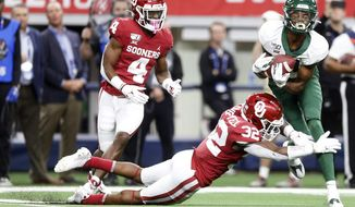 Baylor wide receiver Tyquan Thornton (81) makes a catch as Oklahoma cornerback Jaden Davis (4) and safety Delarrin Turner-Yell (32) defend during an NCAA college football game for the Big 12 Conference championship, Saturday, Dec. 7, 2019, in Arlington, Texas. (Ian Maule/Tulsa World via AP)