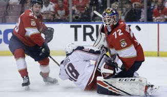 Florida Panthers goaltender Sergei Bobrovsky (72) defends the goal as Columbus Blue Jackets center Pierre-Luc Dubois (18) collides with him during the first period of an NHL hockey game, Saturday, Dec. 7, 2019, in Sunrise, Fla. Panthers' Aleksi Saarela (28) looks on. (AP Photo/Lynne Sladky)