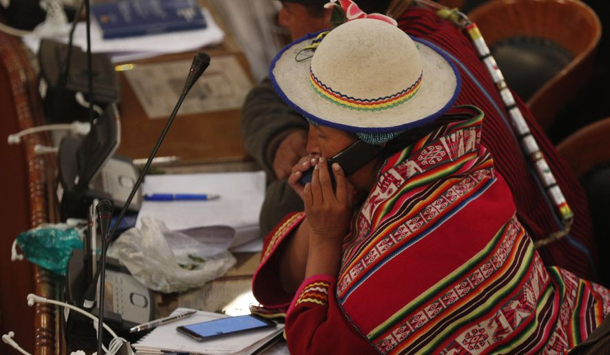 A lawmaker from the MAS party speaks on her cell phone in the Chamber of Deputies where lawmakers are debating a law that would give amnesty to former President Evo Morales in La Paz, Bolivia, late Thursday, Dec. 5, 2019. The interim government of Bolivia warned that it will veto a legislative initiative that would grant an amnesty to Morales, currently exiled in Mexico, if approved by Congress where Morales' party MAS has majority. (AP Photo/Juan Karita)