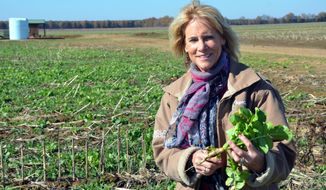 Annie Dee holds a turnip she uses as a cover crop at the Dee River Ranch in Aliceville, Ala. on Nov. 25, 2019.  Dee, who runs the Dee River Ranch in Pickens County, is one of a growing number of farmers who are signed up to get paid to sequester carbon in the soil using what are being called regenerative farm techniques.(Dennis Pillion/Press-Register via AP)