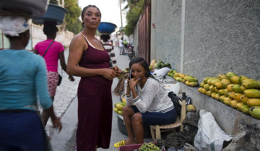 In this Nov. 27, 2019 photo, Wadlande Pierre, right, talks on her mobile phone as she helps her mother, Vanlancia Julien, center, at their fruit and vegetable stand on a sidewalk in Delmas, a district of in Port-au-Prince, Haiti. Pierre, 23, said she temporarily moved in with her aunt in the southwest town of Les Cayes to escape the violent protests in Port-au-Prince. However, she had to move back to the capital because there was no gas, power or water in Les Cayes, and food was becoming scarce. (AP Photo/Dieu Nalio Chery)