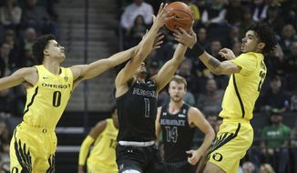 Oregon's Will Richardson, left, and Addison Patterson, right, work against Hawaii's Drew Buggs, center, for the ball during the first half of an NCAA college basketball game in Eugene, Ore., Saturday, Dec. 7, 2019. (AP Photo/Chris Pietsch)