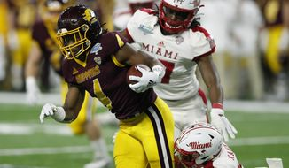 Central Michigan running back Kobe Lewis (4) is tackled by Miami of Ohio's Zach Kahn (29) during the first half of the Mid-American Conference championship NCAA college football game, Saturday, Dec. 7, 2019, in Detroit. (AP Photo/Carlos Osorio)