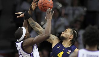 Marquette forward Theo John (4) blocks a shot by Kansas State forward Makol Mawien (14) during the first half of an NCAA college basketball game in Manhattan, Kan., Saturday, Dec. 7, 2019. (AP Photo/Orlin Wagner)