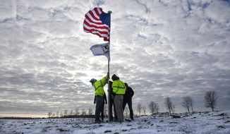 Members of the Krippner family raise a flag Friday, Dec. 6, 2019, in tribute to victims of a Minnesota National Guard Blackhawk helicopter crash that happened on their land near Kimball, Minn. Three soldiers were killed in Thursday's crash at the edge of a farm field about 30 miles south of St. Cloud. (Dave Schwarz/St. Cloud Times via AP)