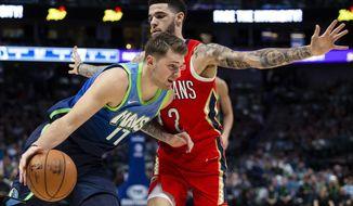 Dallas Mavericks forward Luka Doncic (77) dribbles the ball as New Orleans Pelicans guard Lonzo Ball (2) defends during the first quarter of an NBA basketball game Saturday, Dec. 7, 2019 in Dallas. (AP Photo/Sam Hodde)