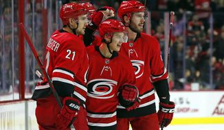 Carolina Hurricanes' Sebastian Aho (20) celebrates his goal against the Minnesota Wild with teammates Nino Niederreiter (21) and Joel Edmundson, right, during the second period of an NHL hockey game in Raleigh, N.C., Saturday, Dec. 7, 2019. (AP Photo/Karl B DeBlaker)