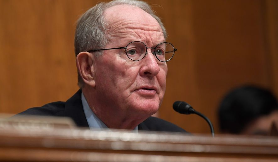 """Sen. Lamar Alexander, Tennessee Republican, called the deal on the surprise medical bills and raising tobacco purchasing age """"a very good Christmas present"""" should Congress choose to unwrap it now. (Associated Press)"""