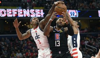 Washington Wizards guard Bradley Beal (3) and guard Ish Smith, right, battle for the ball next to Los Angeles Clippers forward Paul George (13) during the first half of an NBA basketball game, Sunday, Dec. 8, 2019, in Washington. (AP Photo/Nick Wass) ** FILE **