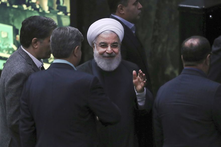Iranian President Hassan Rouhani, center, waves as he leaves the parliament after submitting next year's budget bill, in Tehran, Iran, Sunday, Dec. 8, 2019. Rouhani said his country will depend less on oil revenue next year, in a new budget that is designed to resist crippling U.S. trade embargoes. (AP Photo/Vahid Salemi)