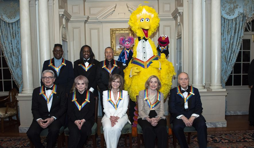 """Front row from left, 2019 Kennedy Center Honorees Michael Tilson Thomas, Linda Ronstadt, Sally Field, Joan Ganz Cooney, and Lloyd Morrisett, back row from left, Philip Bailey, Verdine White, Ralph Johnson, and characters from """"Sesame Street,"""" Abby Cadabby, Big Bird, and Elmo pose for a group photo following the Kennedy Center Honors State Department Dinner at the State Department on Saturday, Dec. 7, 2019, in Washington. (AP Photo/Kevin Wolf)"""