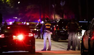 Houston Police Department officers stand by the scene of a shooting in Houston on Saturday, Dec. 7, 2019. A Houston police officer was shot Saturday evening and a suspect was being sought, authorities said. (Marie D. De Jesus/Houston Chronicle via AP)