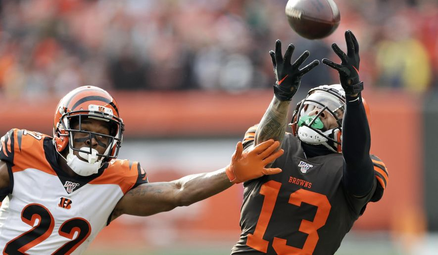 Cleveland Browns wide receiver Odell Beckham Jr. (13) can't hold onto the ball under pressure from Cincinnati Bengals cornerback William Jackson (22) during the first half of an NFL football game, Sunday, Dec. 8, 2019, in Cleveland. (AP Photo/Ron Schwane)