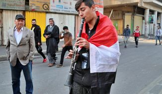 A protester plays an instrument on a street leading to Tahrir Square where ongoing anti-government protests are taking place in Baghdad, Iraq, Sunday, Dec. 8, 2019. At least 25 people, including protesters and police, were killed and 130 wounded on Friday when armed men in pick up trucks stormed Khilani square, which is adjacent to Tahrir, and shot live ammunition at demonstrators. (AP Photo/Hadi Mizban)