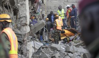 People and rescue workers attend the scene of a building that collapsed in Tasia Embakasi, an east neighbourhood of Nairobi, Kenya on Friday Dec. 6, 2019. A six-story building collapsed in Kenya's capital on Friday, officials said, with people feared to be trapped in the debris. Police say people have been rescued by residents using their bare hands. (AP Photo/Khalil Senosi)